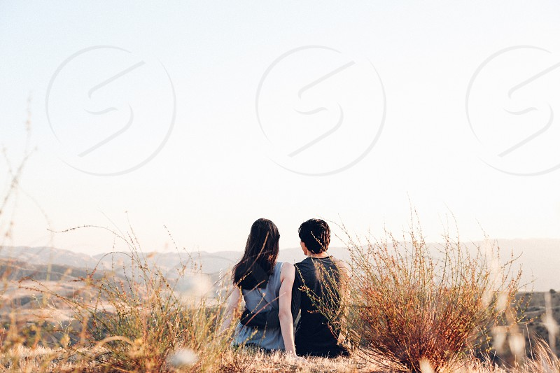 man and woman sitting beside brown grass during daytime photo