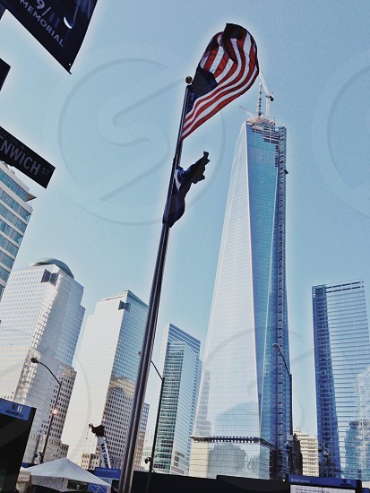 person taking photo of red and white flag in worms eye photography photo