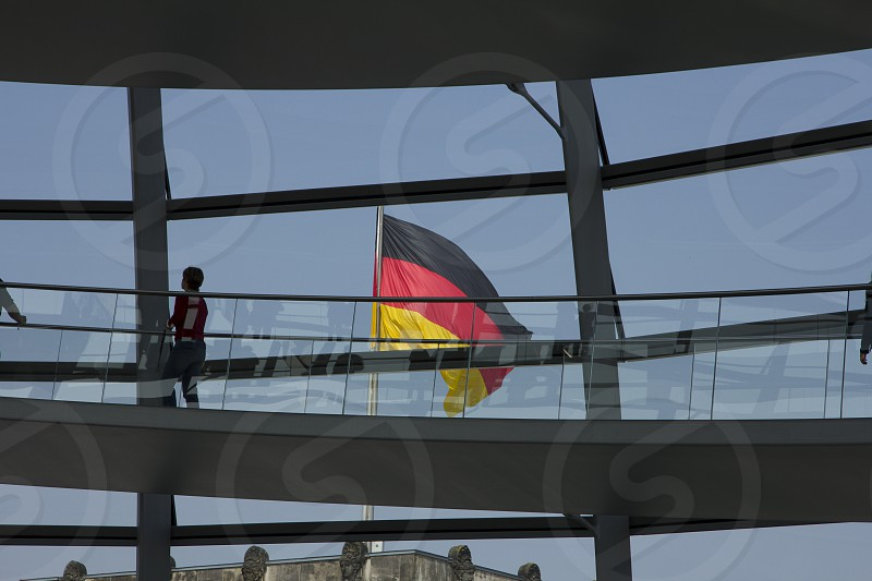 German flag viewed through the glass facade in  Reichstag building - Berlin photo