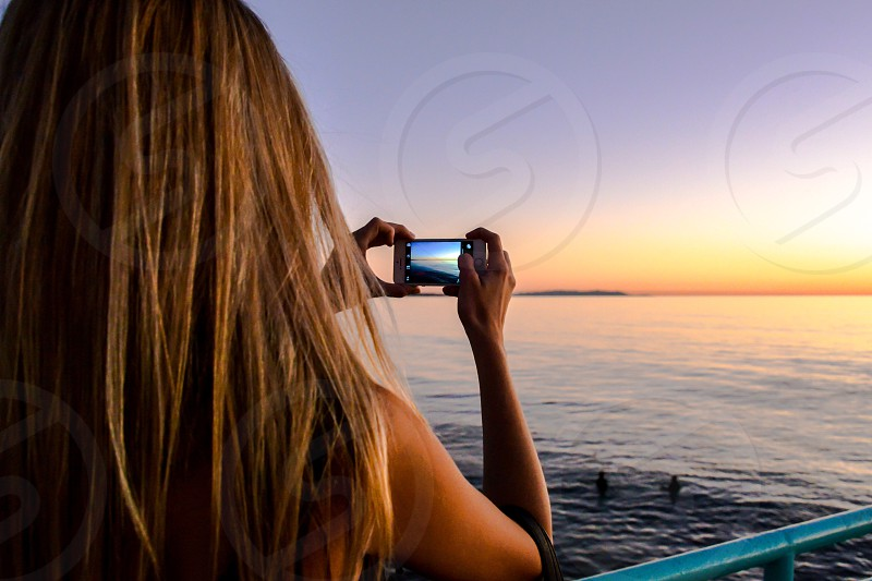 blonde long haired woman capturing sea view at sunrise photo