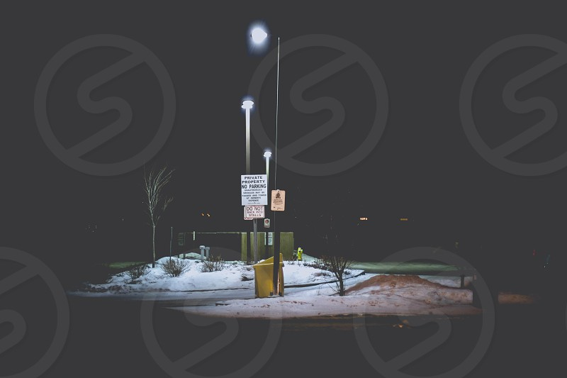grey metal street lamp by grey concrete road at night photo