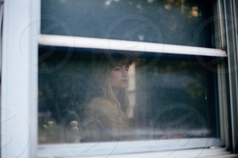 woman in brown shirt looking outside window photo