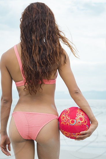 Backside of attractive woman in bikini holding a volleyball at a beach photo