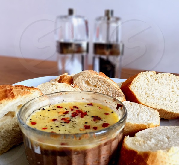 A plate of crusty white bread with a ramekin of pate topped with chilli and black pepper photo