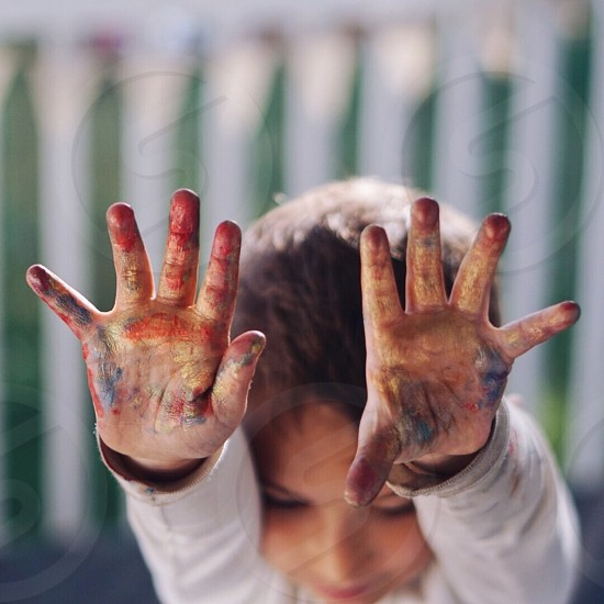 Toddler reaching with painted hands. photo