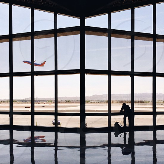 silhouette of person in the airport with red white airplane taking flight photo