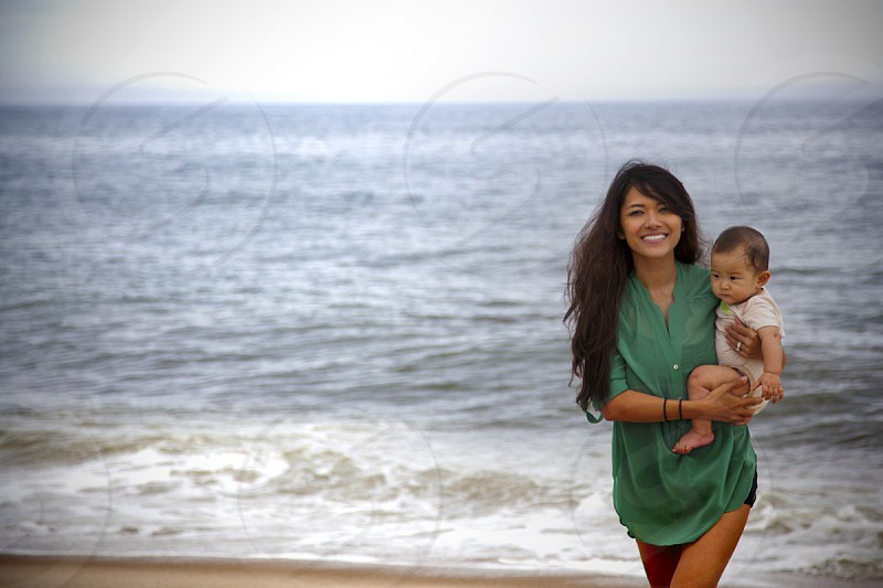 woman with a child walking along the seashore photo