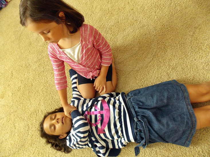 kid in black and white striped long sleeved shirt lying on brown carpet floor photo