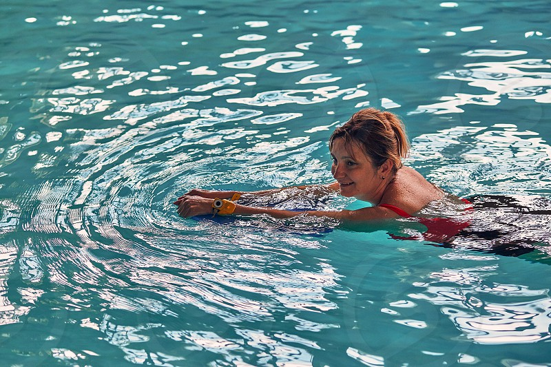 Woman learning to swim practicing in swimming pool using a board. Candid people real moments authentic situations photo