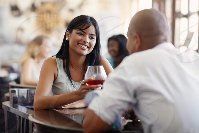 smiling; talking; toast; toasting; cocktail; couple; dating; 20s; adult; alcohol; alcoholic; amusement; beautiful; beverage; boyfriend; brunette; carefree; celebrating; conversation; drink; drinking; emotions; enjoy; female; flirting; fun; girl; girlfriend; glass; guy; happy; hispanic; indoor; joy; latin; latino; laughing; love; male; man; people; pub; relationship; restaurant; shirt; sitting; together; two; woman; young photo
