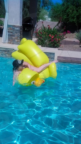 Girl woman giant rubber ducky duck fun laughing laugh laughter swimming pool photo