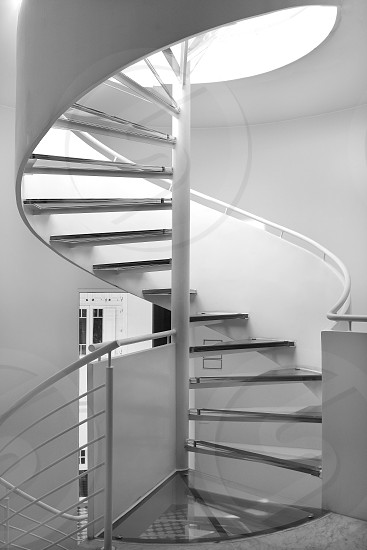 Black and white image of a modern spiral staircase with glass steps. photo
