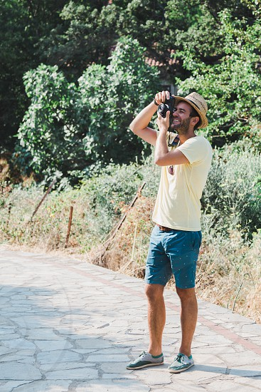Young man taking a photograph in a countryside photo