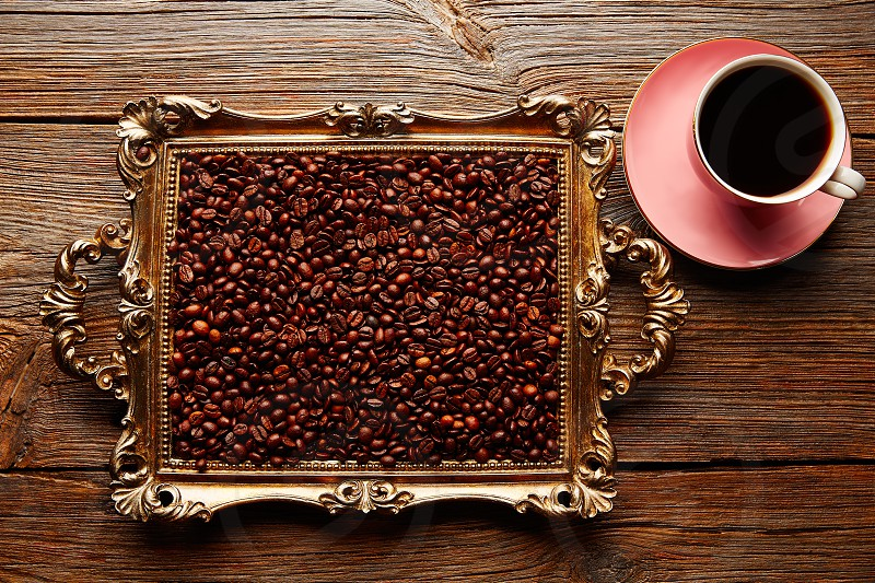 Coffee cup and beans on vintage golden tray in wooden old table photo