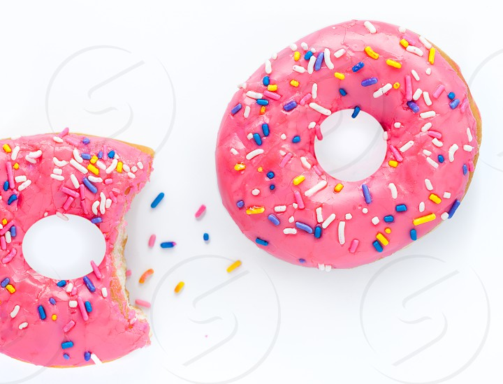 Overhead view of a glazed doughnut with pink frosting and sprinkles on a white surface photo