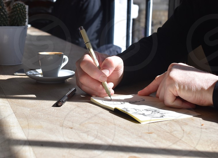 Artist drawing in cafe whilst having a coffee. photo