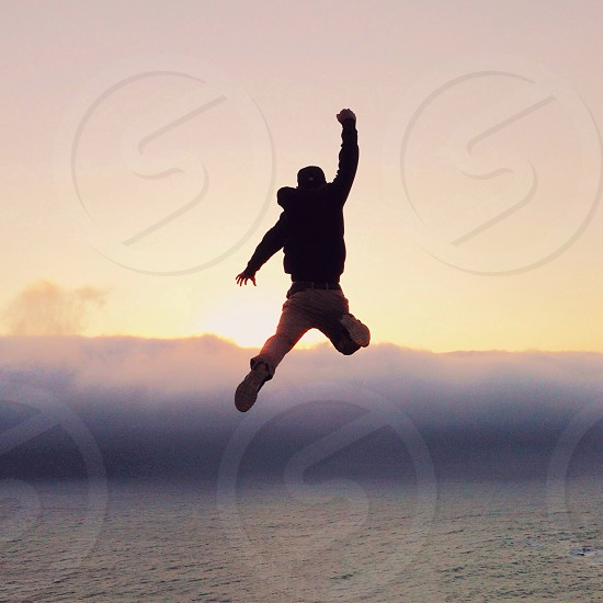 man jumping through the air into water fully clothed photo