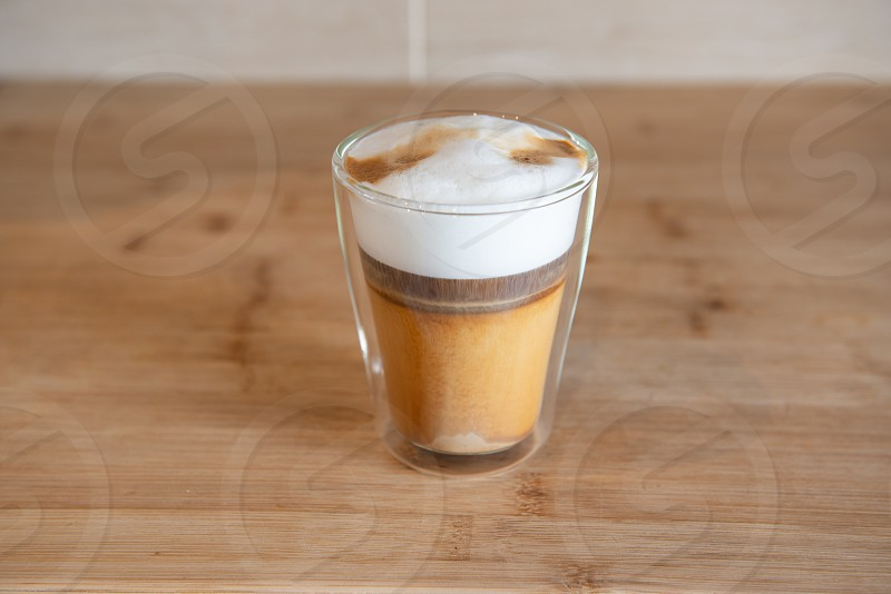 multilayer coffee or cappuccino in a glass cup on wooden table. photo