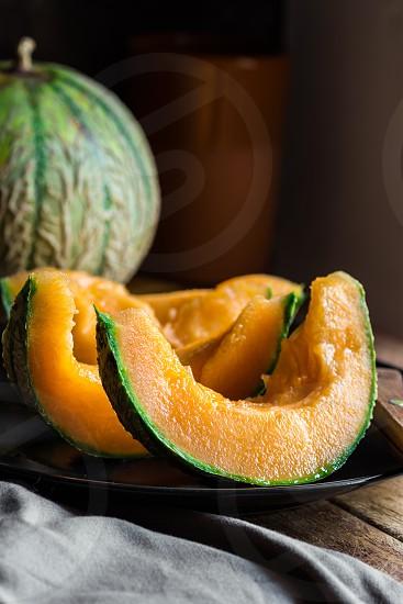 Ripe juicy sliced orange cantaloupe dark plate knife wood kitchen table rustic interior minimalist style photo