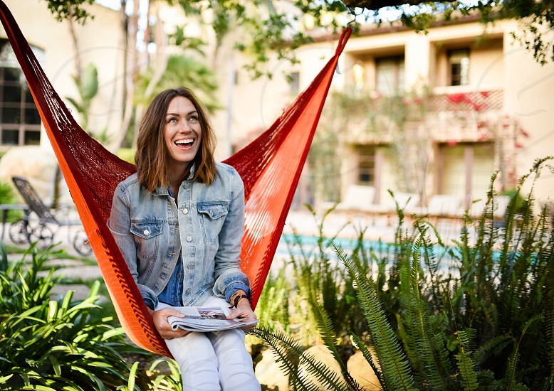 woman in blue denim jacket and white denim jeans sitting in orange cloth hammock surrounded by green plants photo