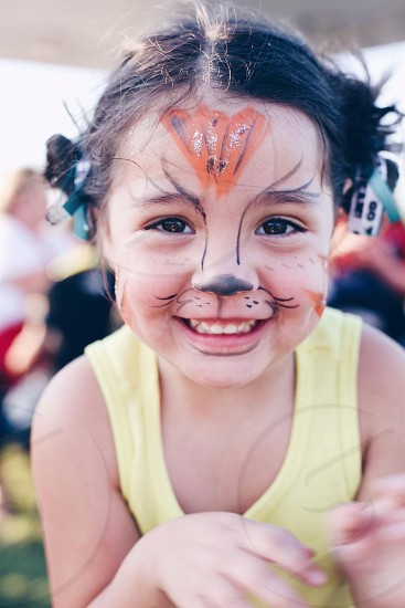 girl in yellow tank top with face paint photo