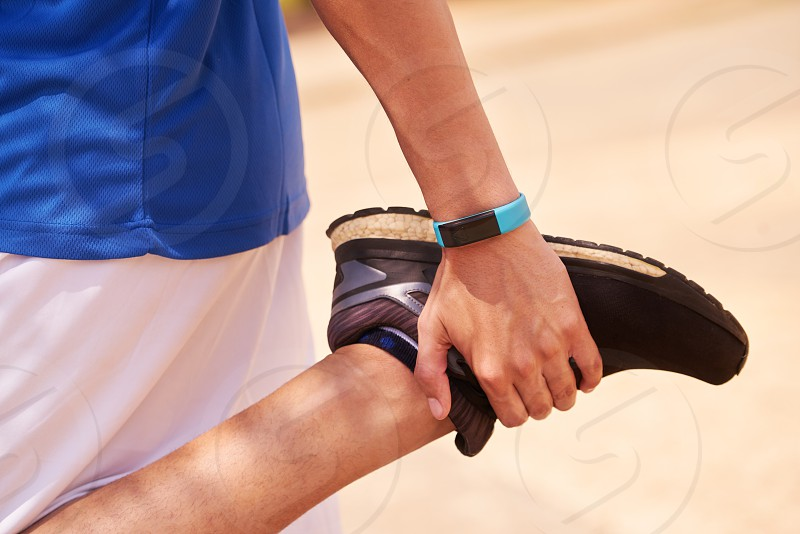 fit; watch; running; sports; jogging; man; stretching; leg; activity; athlete; body; bracelet; closeup; copyspace; copy space; counter; equipment; exercise; exercising; fitwatch; fitband; fitness; fit watch; hand; health; heart; heart beat; hispanic; jogger; leisure; outdoor; people; person; programming; rate; run; runner; smartwatch; sport; sporty; steps; technology; time; tracker; training; wearable; working out; wrist; young photo