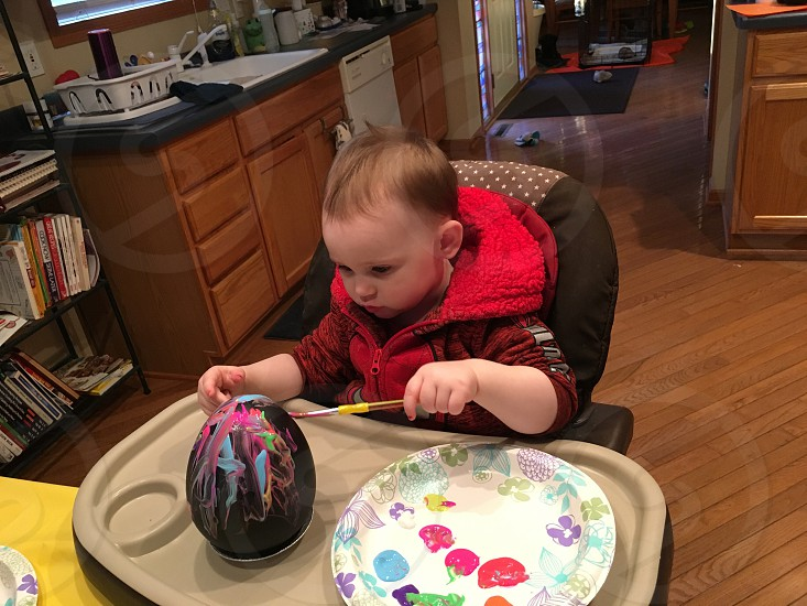 Toddler girl painting an egg photo