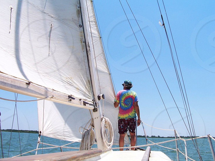 Man in colorful shirt standing on bow of a sailboat as it sails across a lake on a beautiful sunny afternoon. photo