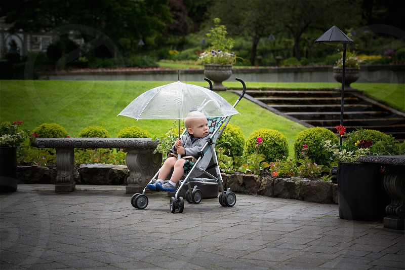 A young boy patiently waits in the rain.  photo