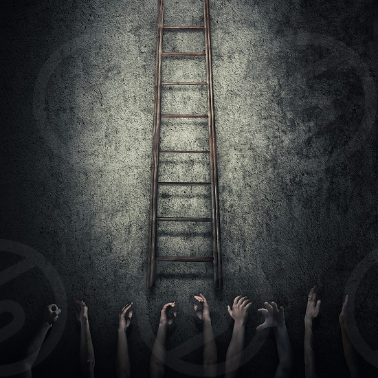 Abstract idea concept as a lot of human hands stretched out to reach a ladder and escape from a dark room prison. Surrounded by limitations danger and fear symbol. photo