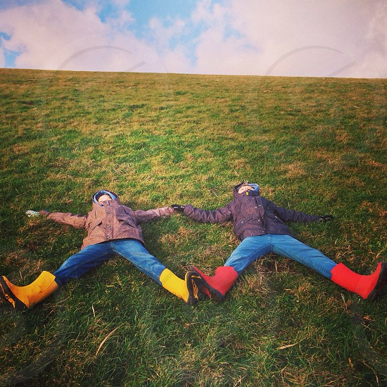 people lying on green grass field photo