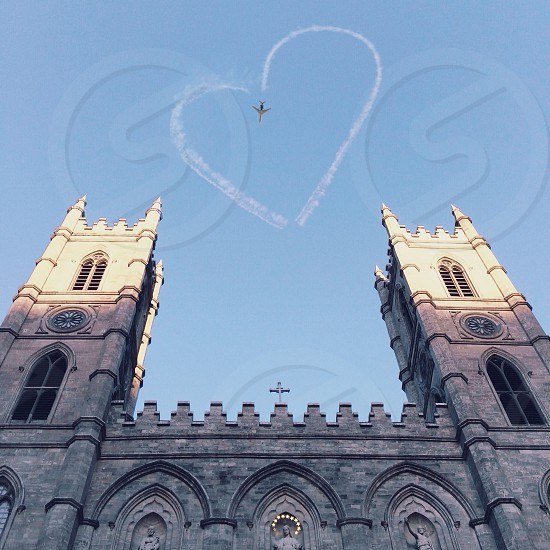 heart shape jet smoke on sky and gray bricked church photo