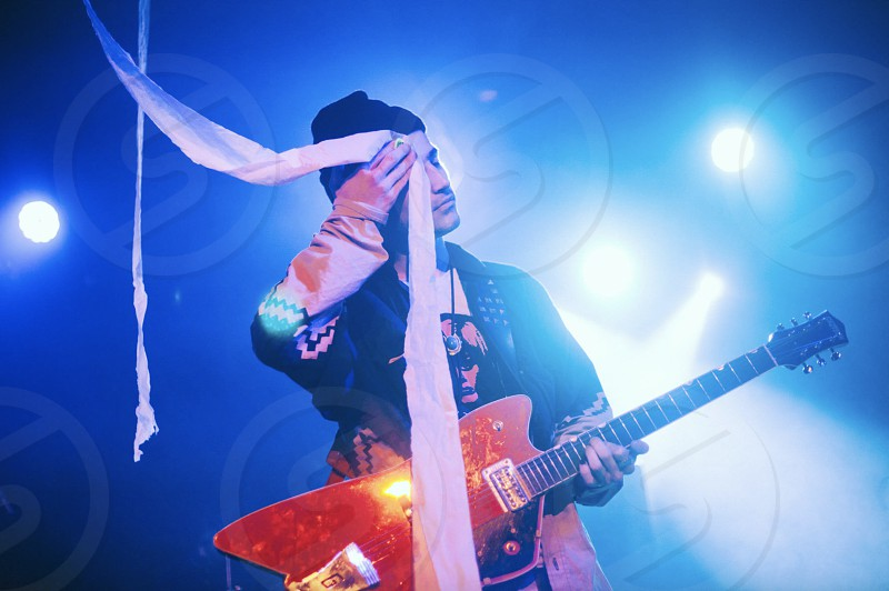 The Black Lips guitarist uses toilet paper to wipe the sweat off of his forehead.  photo