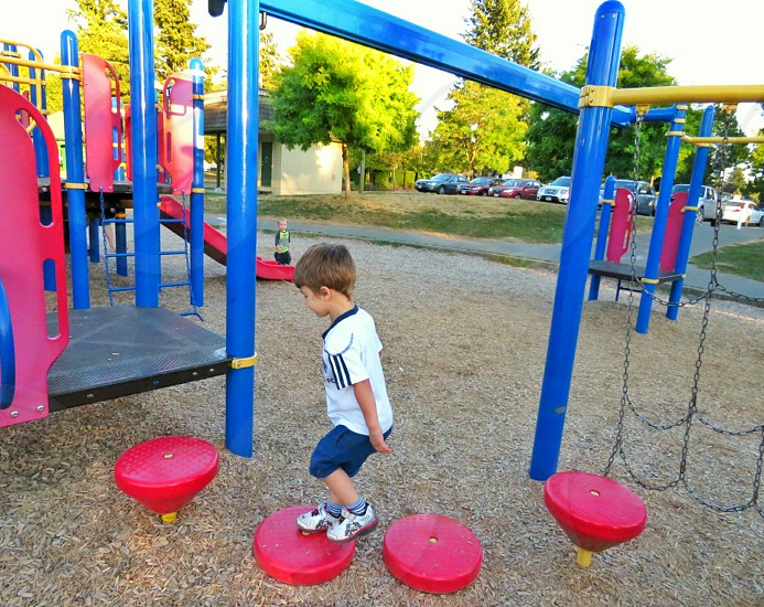 A toddler wearing blue and white summer shorts plays on the red balance stools at the playground. Landscape shot.  photo