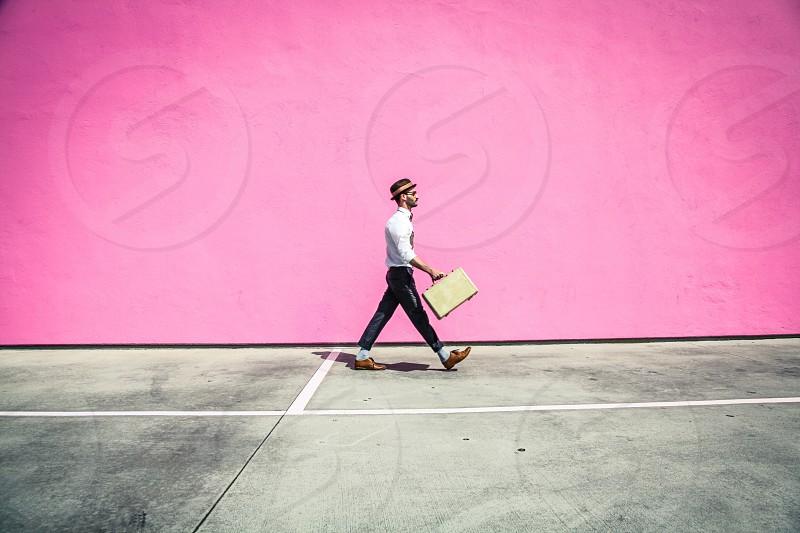 man in white button down long sleeve shirt walking beside pink wall photo