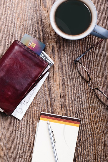 Leather wallet with dollar banknotes credit card and receipt glasses cup of coffee on wooden desk. Portrait orientation photo