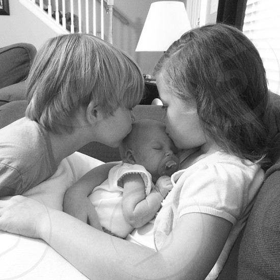 boy and girl kissing a baby photo