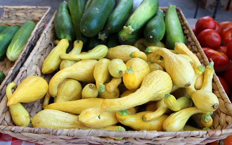 Gnarly yellow squash and cucumbers at farmers market photo