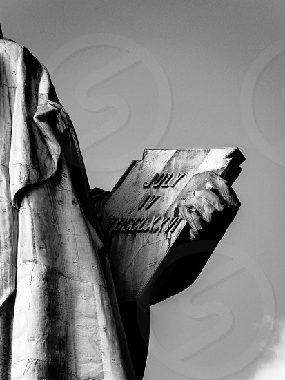 person holding book july 4 statue photo
