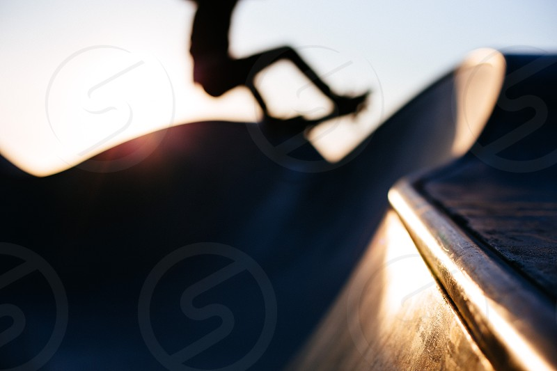 A silhouetted skateboarder does a front side ollie at the skatepark in Venice Beach California.  photo