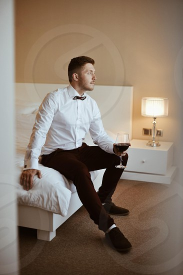 man in white dress shirt sitting on bed holding half filled long stemmed wine glass photo