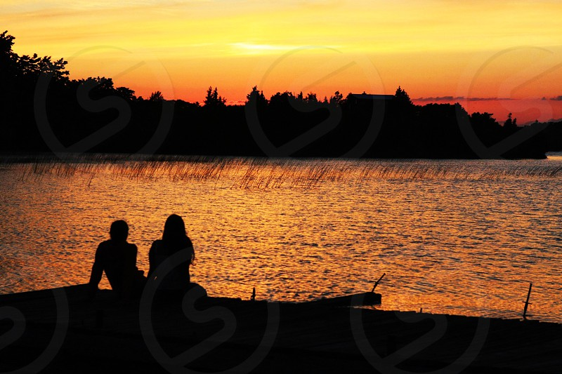 2 person sitting watching sea in sunset photo