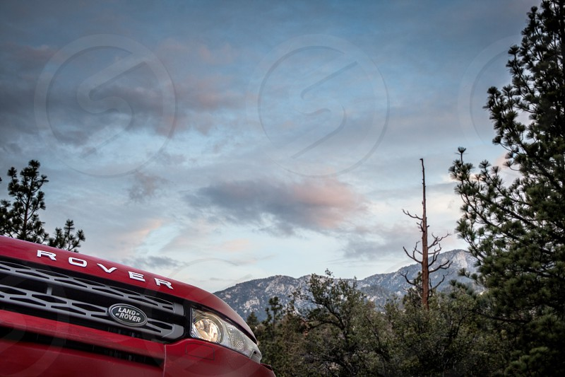 A rover explores  mountain under a canopy of clouds and trees.  Leaves branches dirt dirt off road red explore grill range badge lights. photo