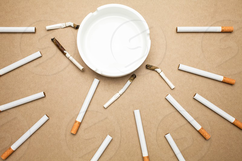 Business goal concept : cigarette and ashtray with brown background photo