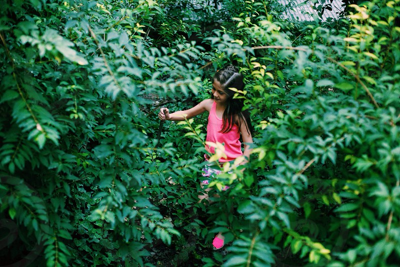 human child with long brown hair playing in between trees photo