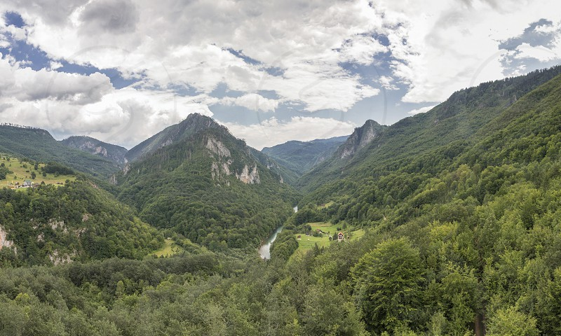Mountain range and small village houses in green forest near Tara river canyon view from Djurdjevica Tara Bridge Montenegro photo