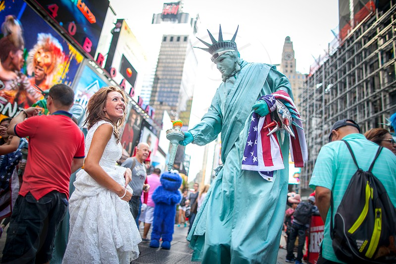 A bride smiles at a lady liberty costume in New York City. Stilts American flag Times Square crowd people strangers sidewalk buildings city. photo