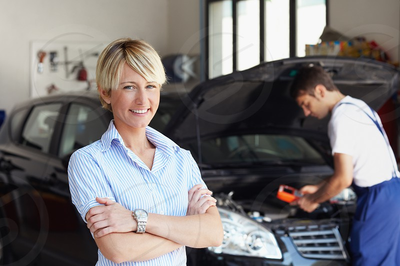 portrait; mechanic; client; woman; man; car; auto repair shop; engine; smiling; happy; people; male; female; Caucasian; young; adult; young man; young woman; mid adult; 30s; arms folded; happiness; confidence; pride; car owner; looking at camera; front view; looking; repairing; working; computer; equipment; indoors; garage; manual worker; transportation; transport; vehicle; bonnet; hood; auto; automobile; motor vehicle; broken car; repair; car repair; fixing; expertise; skill; service photo