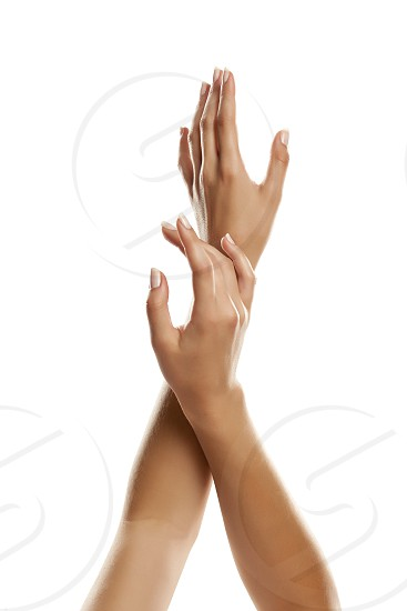 closeup of female hands applying hand cream on white background photo