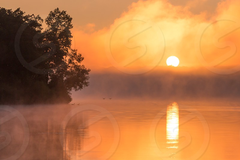 Sunrise over a misty lake photo